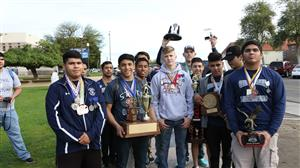The wrestling team poses with their trophies.